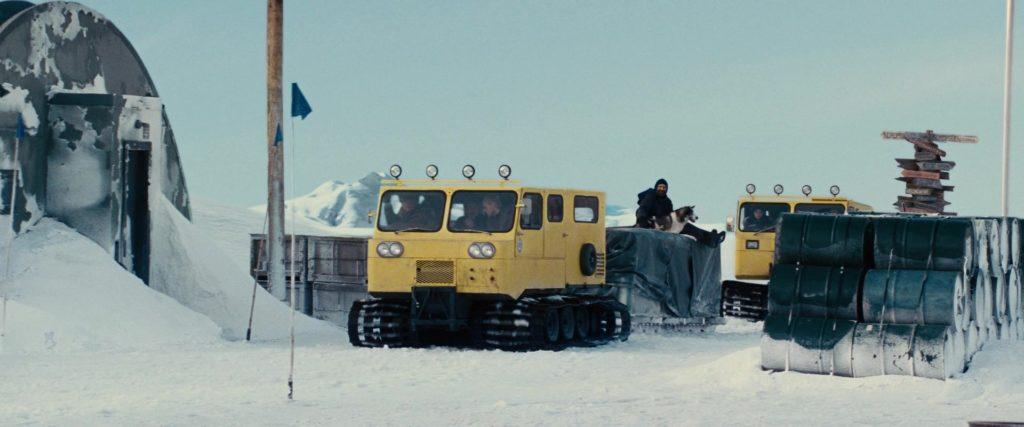 """Кадр их к/ф """"Нечто"""" 2011, снег, антарктида, снегоход, желтый, собакен, бочки с горючим, указатель расстояний"""