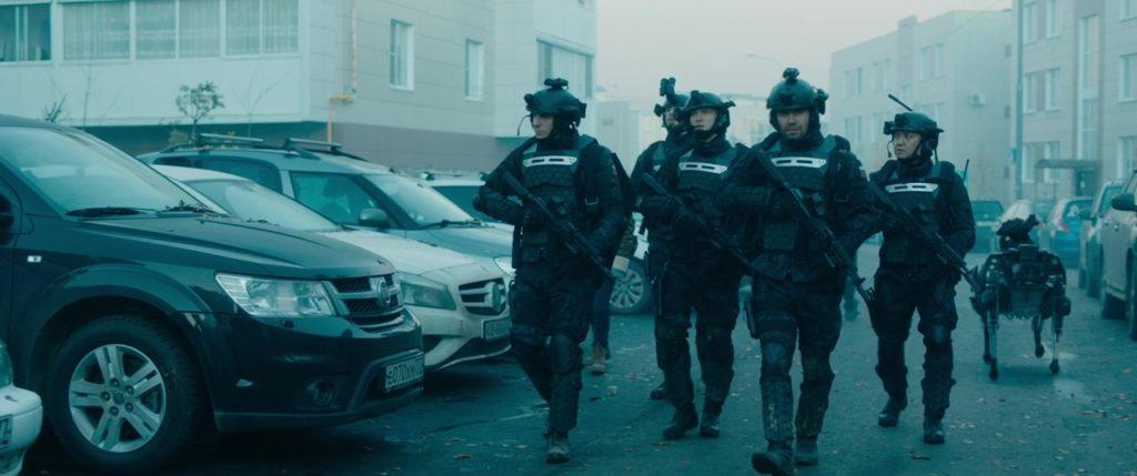 """Кадр из к/ф """"Аванпост"""". Разведгруппа правительственных сил в полной выкладке. За спинами вояк перемещается тяжеловооруженный пулеметчик в экзоскелете."""